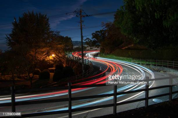 light trails on road against sky at night - naruto stock photos and pictures