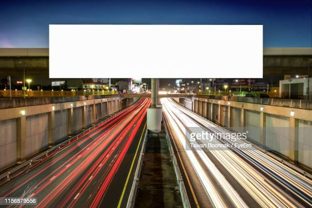 light trails on road against sky at night - billboard stock pictures, royalty-free photos & images