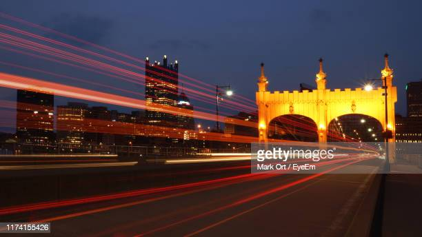 light trails on road against sky at night - pittsburgh stock pictures, royalty-free photos & images