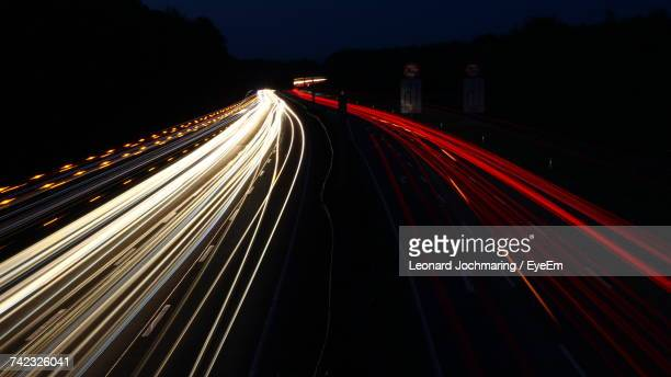 light trails on road against sky at night - vehicle light stock photos and pictures