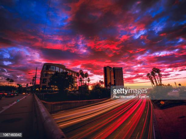 light trails on road against sky during sunset - san fernando california stock photos and pictures