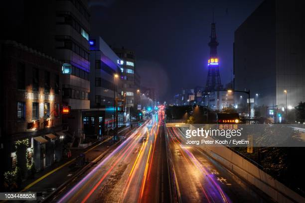 light trails on road amidst buildings in city at night - 札幌市 ストックフォトと画像