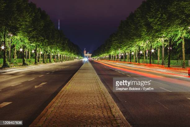 light trails on road amidst trees in city - berlin stock pictures, royalty-free photos & images