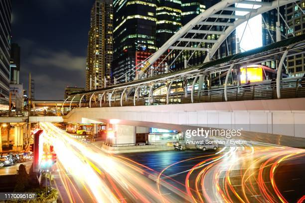 light trails on road at night - anuwat somhan stock photos and pictures
