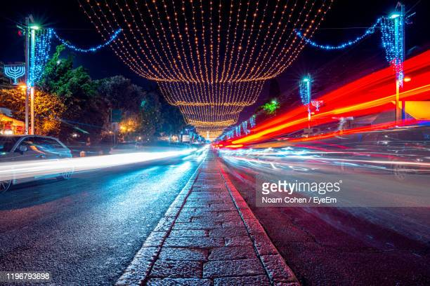 light trails on road at night - noam cohen stock pictures, royalty-free photos & images