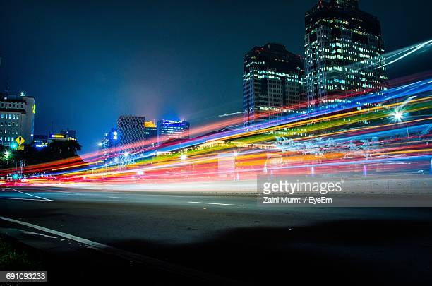light trails on road at night - illuminate stock photos and pictures