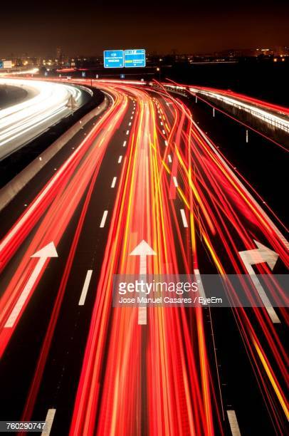 light trails on road at night - red light stock pictures, royalty-free photos & images