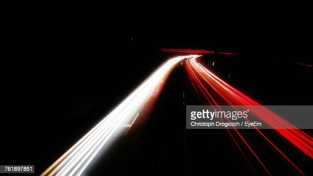 light trails on road at night - vehicle light stock photos and pictures
