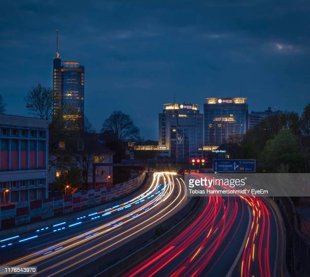 light trails on road by buildings against sky at night - ruhr stock pictures, royalty-free photos & images
