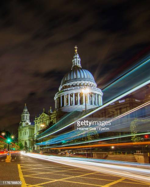 light trails on road by buildings against sky at night - heather cole stock pictures, royalty-free photos & images