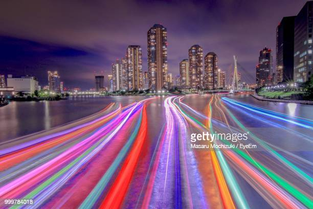 Light Trails On Road By Illuminated Buildings Against Sky At Night
