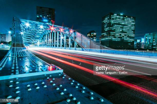 light trails on road by illuminated buildings in city at night - 永代橋 ストックフォトと画像