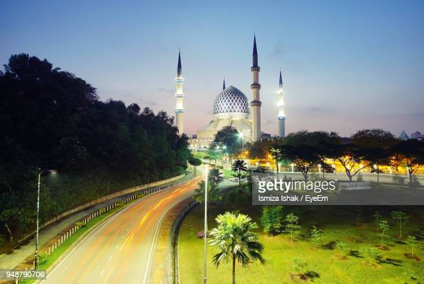 Light Trails On Road By Illuminated Mosque Against Sky
