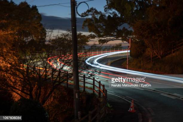 light trails on road by trees against sky at night - naruto stock photos and pictures