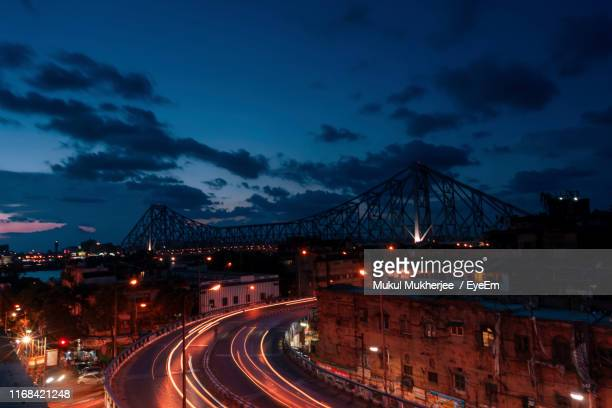 light trails on road in city against sky at night - west bengal stock pictures, royalty-free photos & images