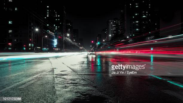 light trails on road in city at night - wet stock pictures, royalty-free photos & images
