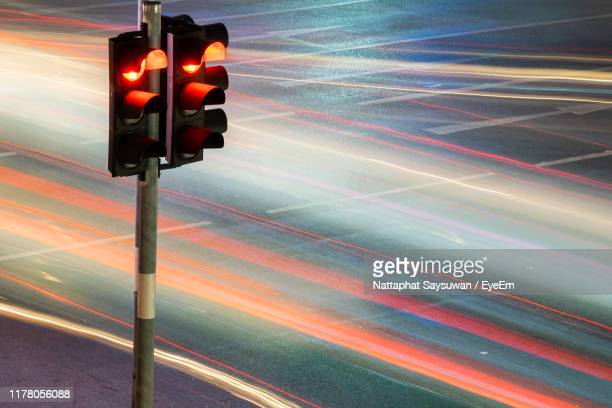 light trails on road - red light stock pictures, royalty-free photos & images
