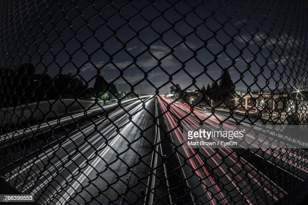 Light Trails On Road Seen Through Chainlink Fence At Night