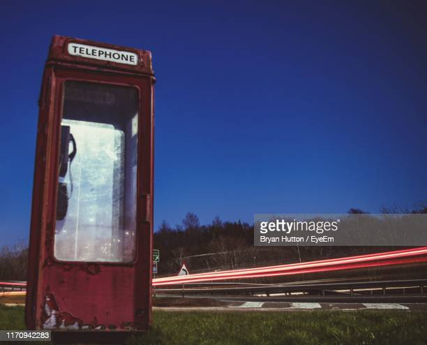 Light Trails On Road Telephone Booth By Against Clear Sky At Night