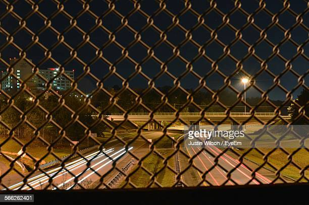 Light Trails On Road Under Bridge See From Chainlink Fence At Night