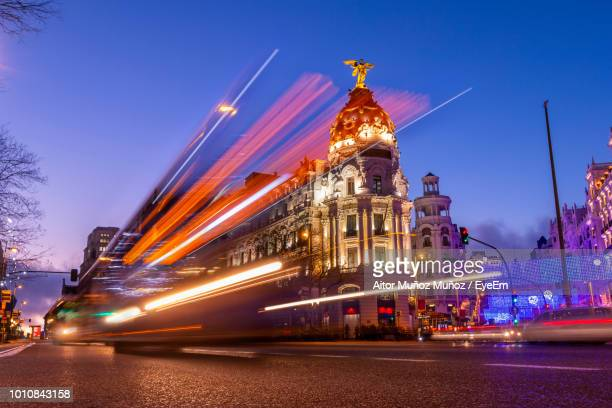 light trails on street against buildings at night - madrid stock-fotos und bilder