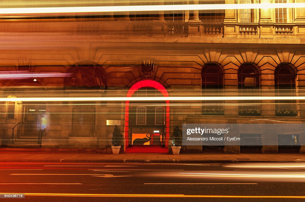 Light Trails On Street Against Illuminated Building : Stock Photo