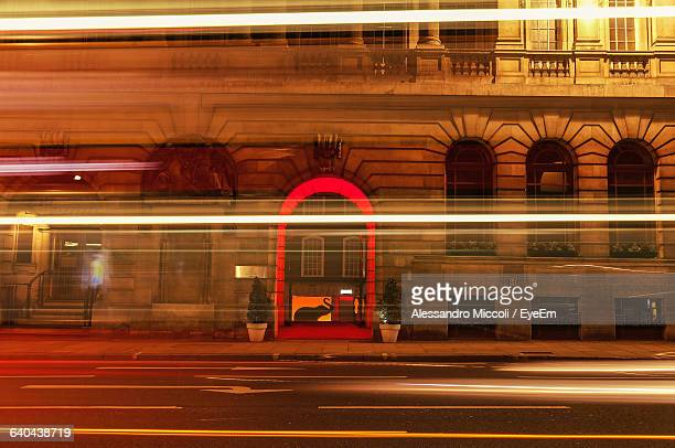 light trails on street against illuminated building - alessandro miccoli stockfoto's en -beelden
