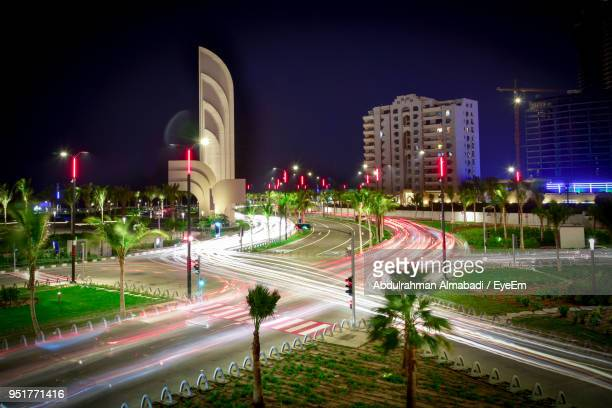 light trails on street amidst buildings in city at night - jiddah stock pictures, royalty-free photos & images