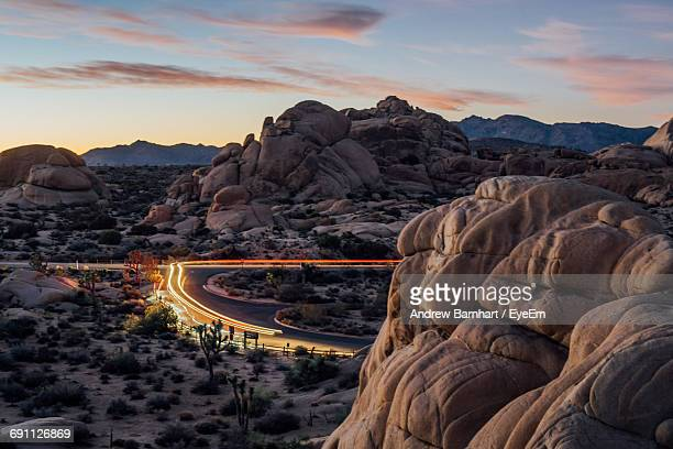 Light Trails On Street Amidst Rock Formations