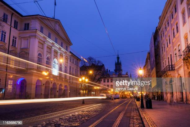 light trails on street at night in lviv, ukraine - neo classical stock pictures, royalty-free photos & images