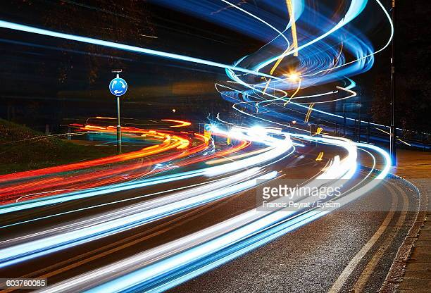 light trails on street at night - light trail stock photos and pictures