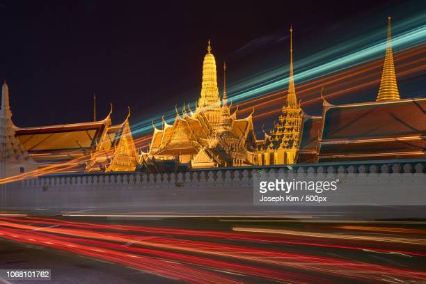 light trails on street by royal palace, bangkok, thailand - grand palace bangkok stock pictures, royalty-free photos & images