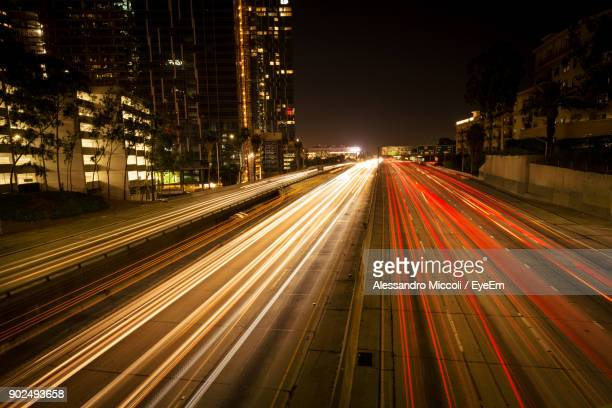 light trails on street in city at night - alessandro miccoli stock photos and pictures