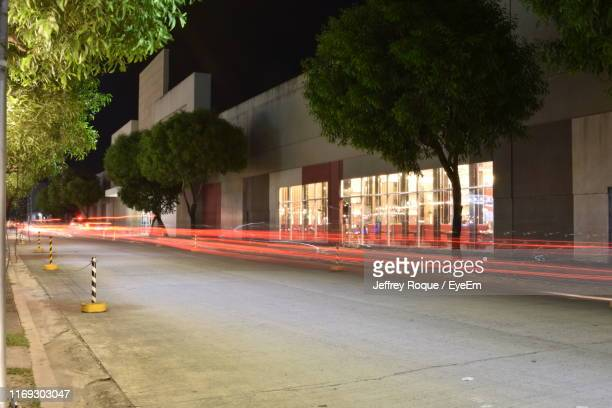 light trails on street in city - jeffrey roque stock photos and pictures