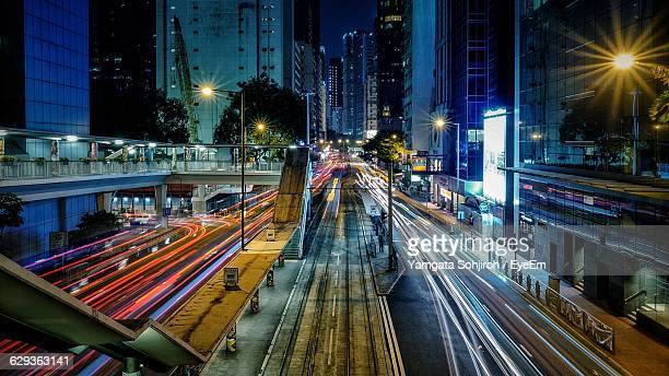 light trails on street with railroad station at wan chai - wanchai stock photos and pictures