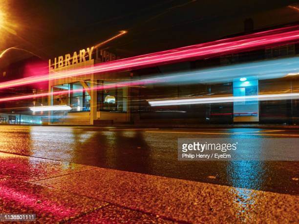 light trails on wet street at night - henry street stock pictures, royalty-free photos & images