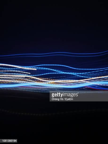 light trails over black background - strom stock-fotos und bilder