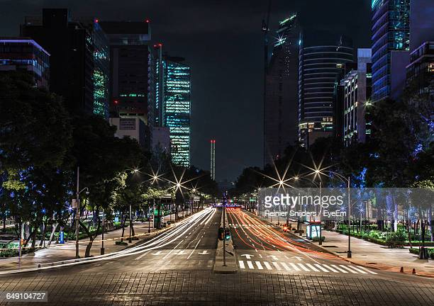 Light Trails Over Illuminated Street Amidst Buildings In City At Night
