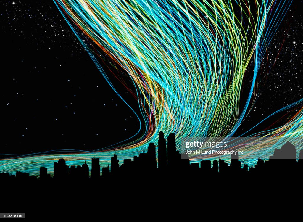 Light trails over silhouette of city skyline : Stock Photo