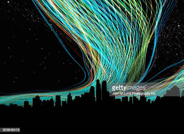 light trails over silhouette of city skyline - data stream stock photos and pictures