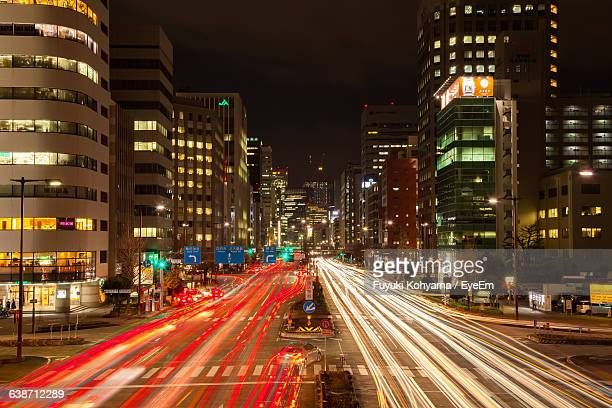 Light Trails Over Street Amidst Illuminated Buildings At Night