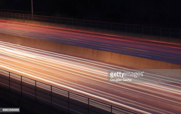 Light trails paint the highway with moving headlights