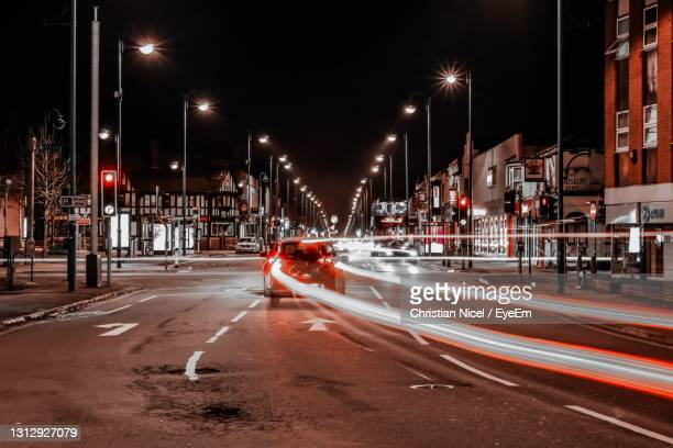 light trails through busy town at night - adobe stock pictures, royalty-free photos & images