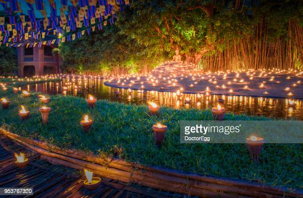 light up candle in buddhist day festival at wat phan tao temple, thailand - loi krathong stock photos and pictures