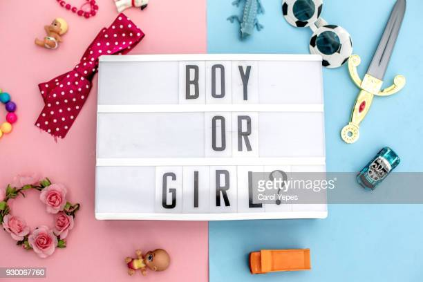 "lightbox with "" boy or girl""  message.Clichés concept. Femeninine and masculine toys."