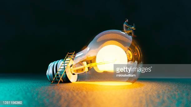 het concept van de gloeilamp met mensenzitting bovenop het het krijgen van grote ideeën - idee stockfoto's en -beelden