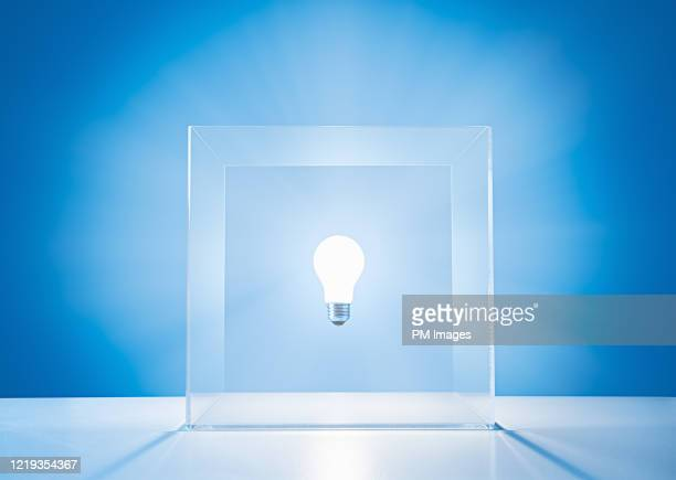 lightbulb in a clear box - hovering stock pictures, royalty-free photos & images