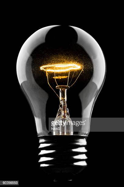 lightbulb on black - filament stock photos and pictures