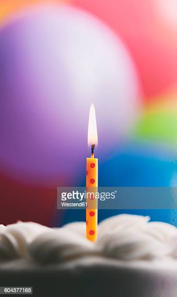 lighted birthday candle on a cake in front of balloons - birthday balloons stock photos and pictures
