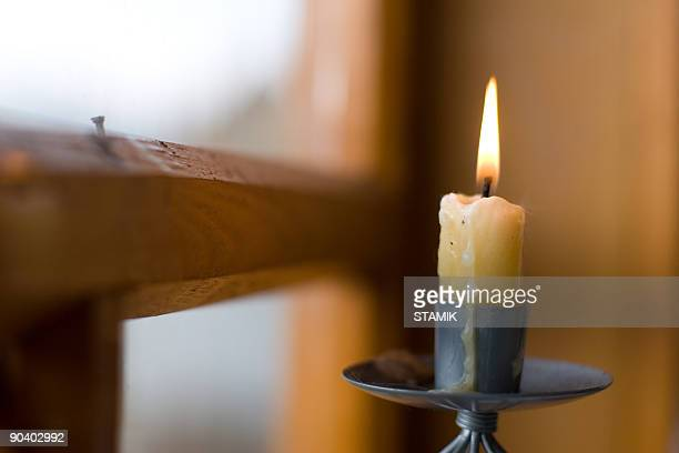 A lighted candle stick near a window